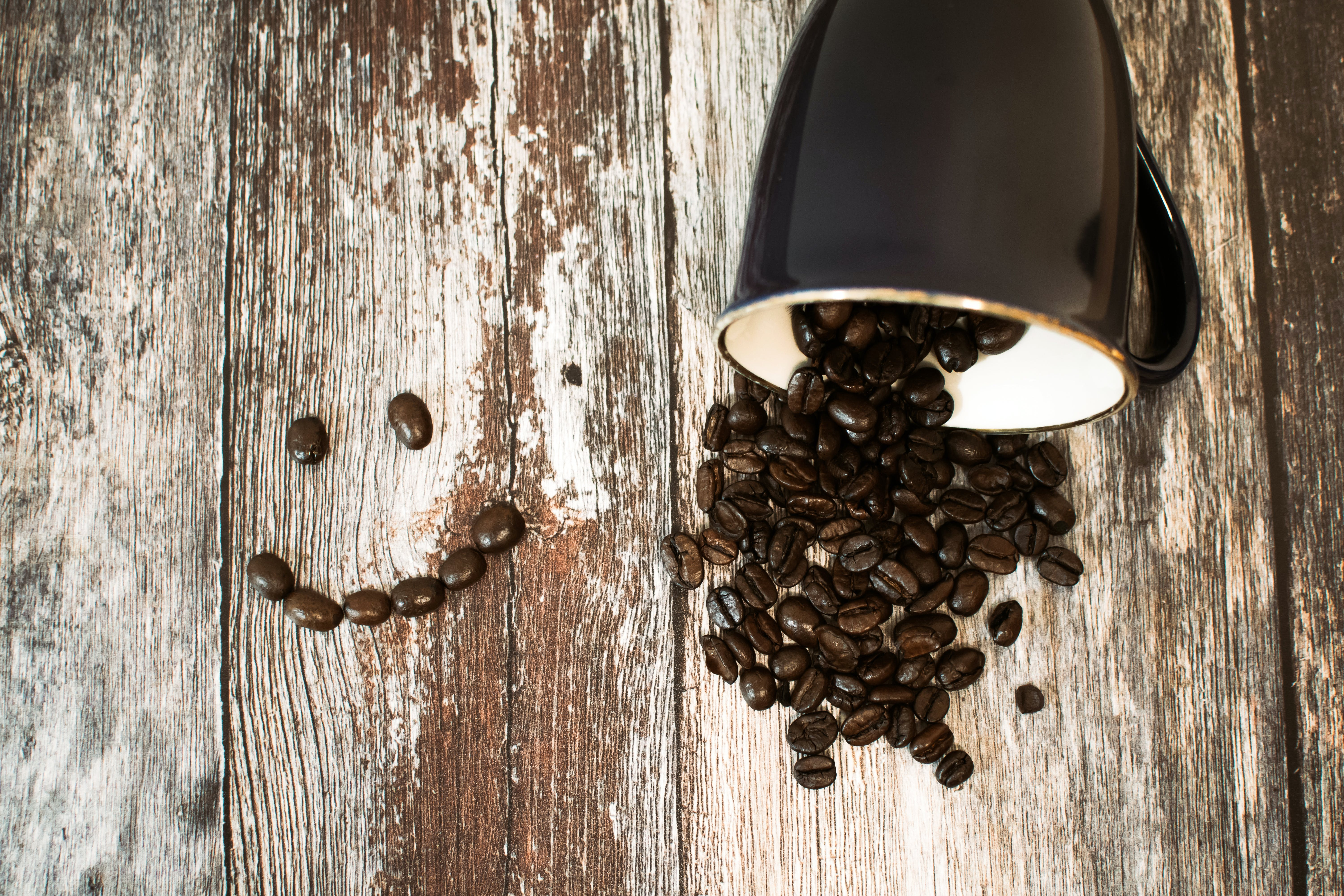 Black Ceramic Cup With Coffee Beans All on Brown Wooden Surface