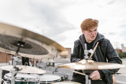 Man in Black Leather Jacket Playing Drums
