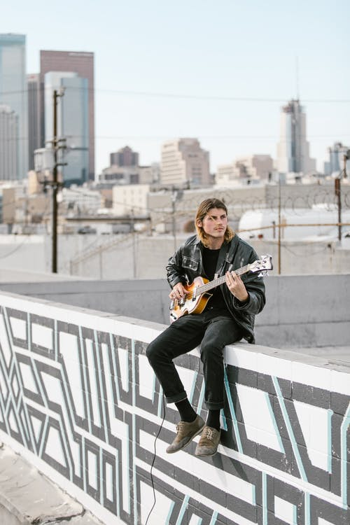 Man in Black Jacket and Black Pants Playing Guitar Sitting on White Concrete Fence
