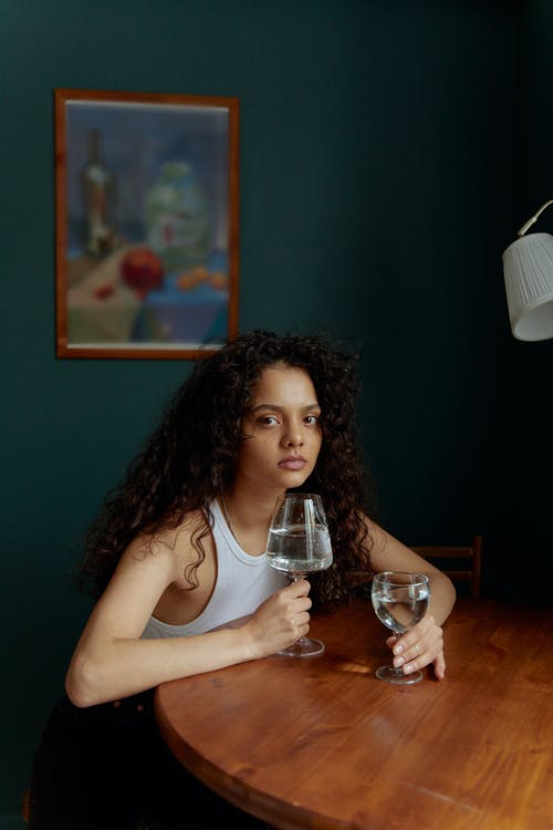 Beautiful Woman Holding Wine Glass on Top of Wooden Table