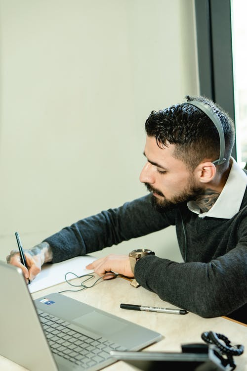 Man in Black Sweater Writing on White Paper