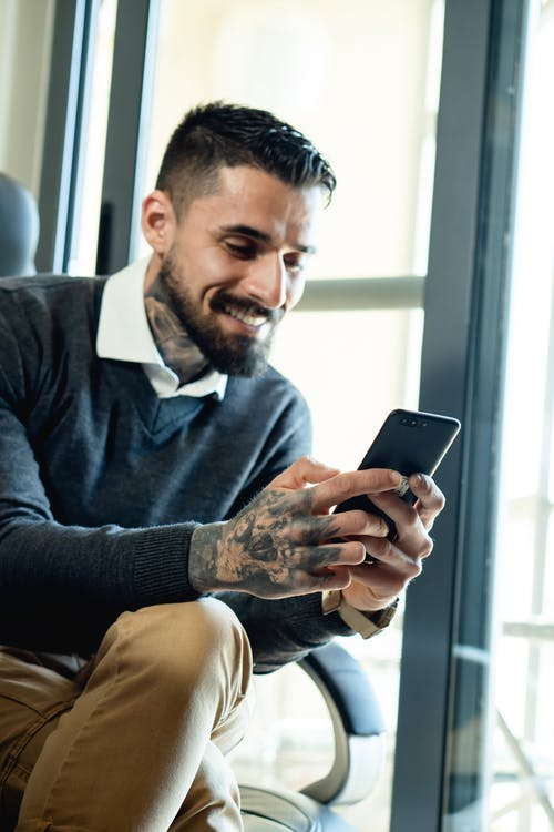 Smiling Bearded Man Using a Cellphone