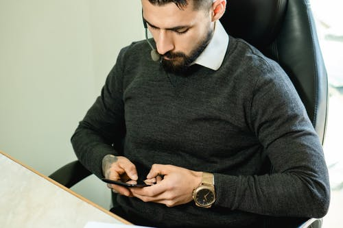 Man in Sweater Using a Cellphone