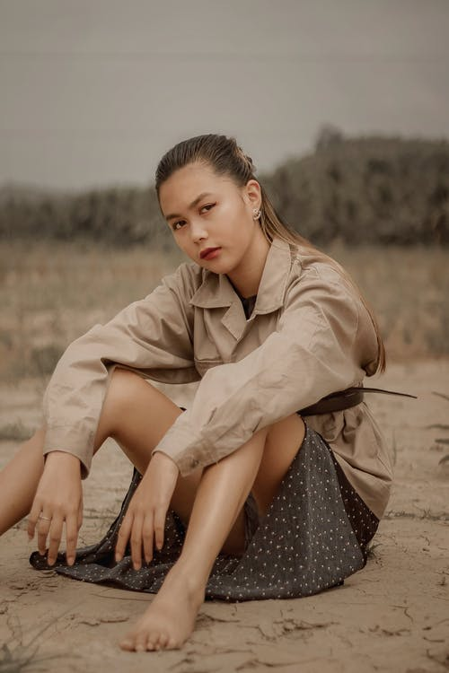 Barefoot young ethnic female in safari jacket sitting on land while looking at camera in daytime
