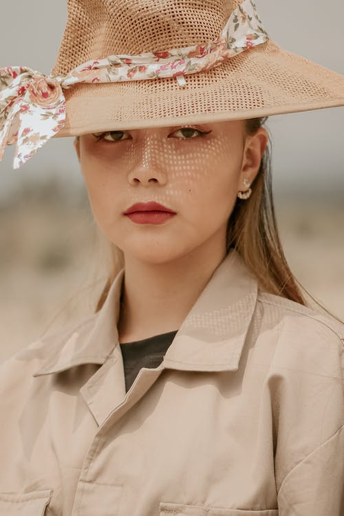 Asian model in retro hat with floral ornament