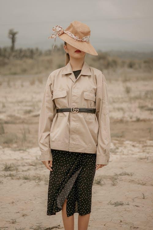 Unrecognizable model in retro wear on dry terrain