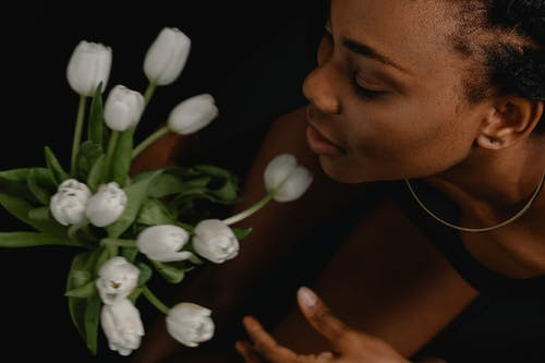 A Close-Up Shot of a Woman Holding White Tulips