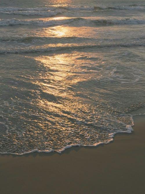 Ocean Waves Crashing on Shore at Sunset