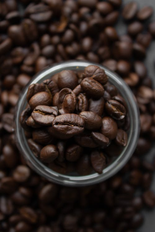 Coffee beans scattered on table near glass cup