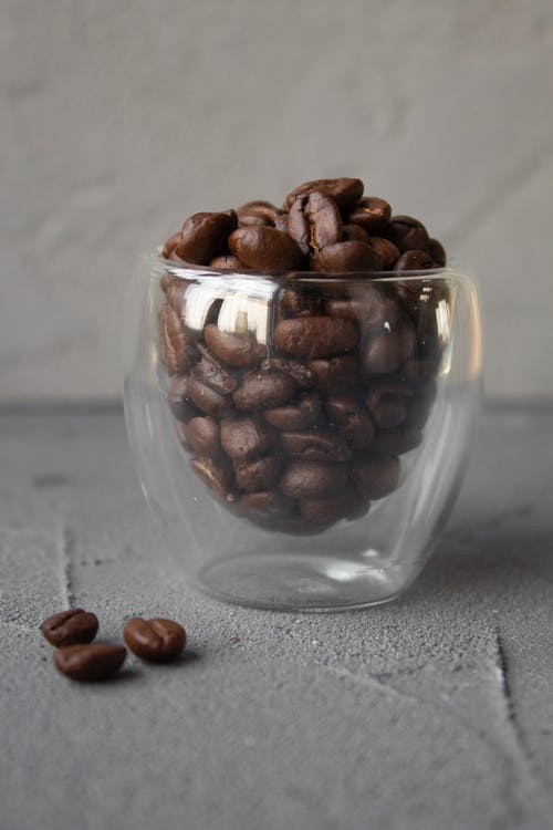 Pile of brown coffee beans in glass cup on table