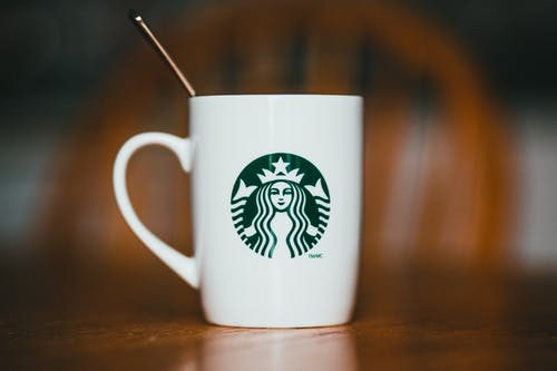 Closeup of white ceramic mug with logotype of brand with hot drink and teaspoon placed on wooden table