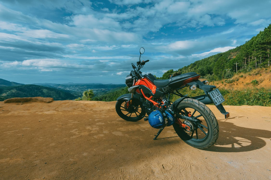 Photography of Orange and Black Sports Motorcycle Near a Cliff
