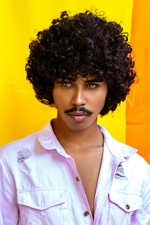 Trendy young ethnic male in shirt with curly hair looking away on two color background