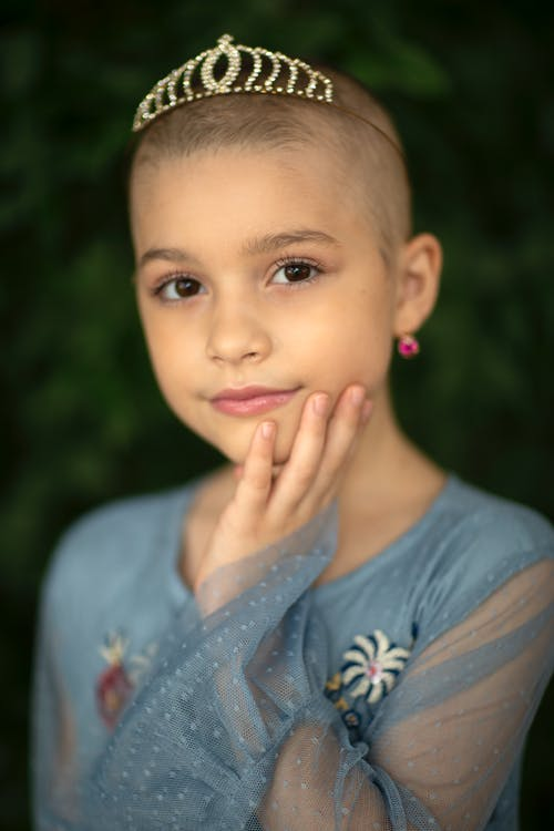 Gentle girl with shaved head touching face