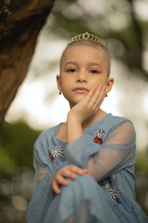 Gentle child in dress and crown on shaved head touching cheek while looking at camera during brain cancer recovery