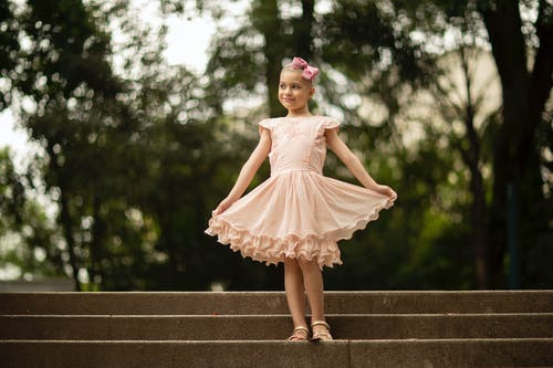 Smiling kid in ruffled dress and headband with bow looking away on park stairs during brain cancer recovery