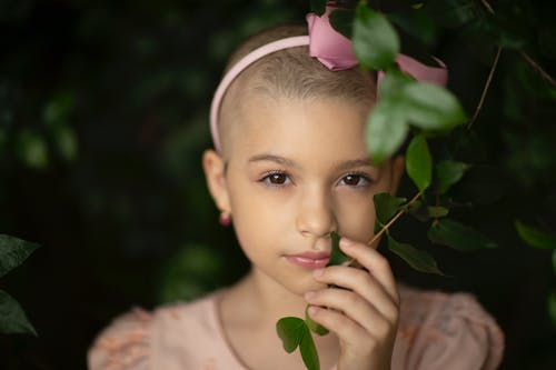 Tender kid in headband with bow touching green plant sprig while looking at camera during brain cancer recovery in park