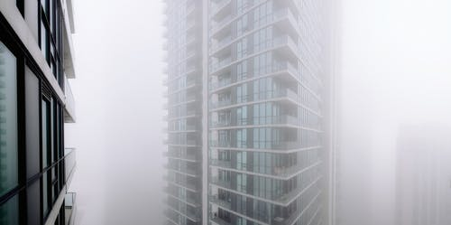Contemporary residential building with balconies covered with thick fog located on street of modern city with houses in overcast weather