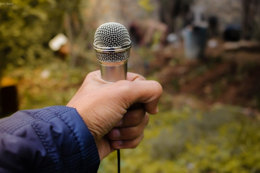 Person Holding Grey Corded Microphone in Selective Focus Photography Photo Taken