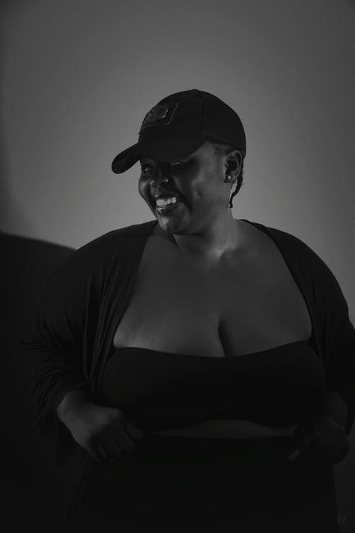 Woman in Black Scoop Neck Shirt Wearing Black Cap