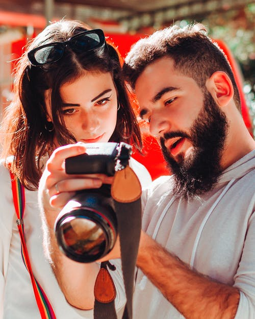 Male photographer showing pictures to female client