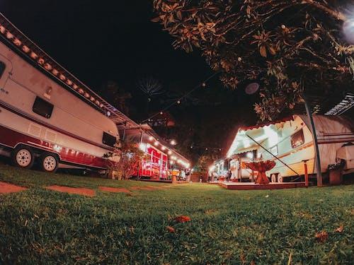 Illuminated caravans parked at campsite at night
