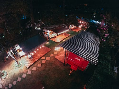 Aerial view of trailers for tourists at camping area decorated with sparkling garlands at night