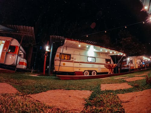 Vans with glowing lights at camping area