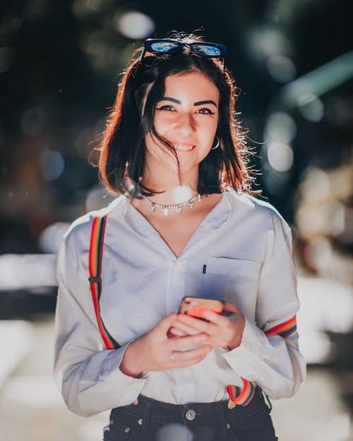 Cheerful young ethnic female with dark hair in casual clothes smiling and looking at camera while messaging on mobile phone standing on city street on sunny day