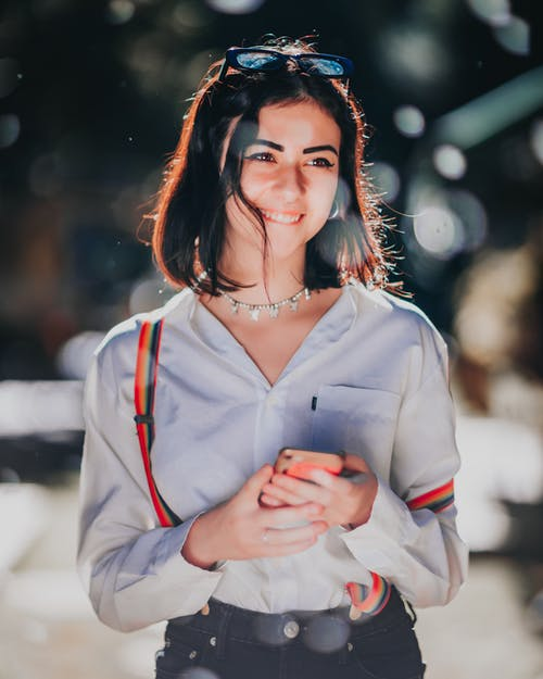 Happy ethnic female teenager messaging on smartphone and smiling on street