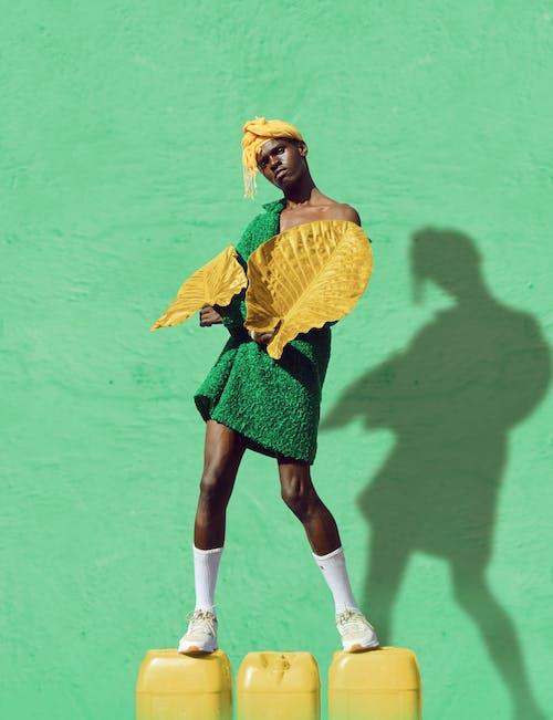 Woman in Yellow Long Sleeve Shirt and Green Skirt Standing Beside Green Wall