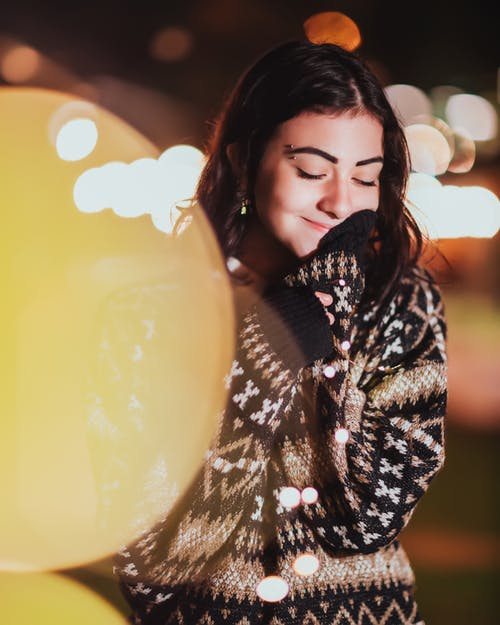 Attractive young woman in warm patterned sweater standing with closed eyes on street at night