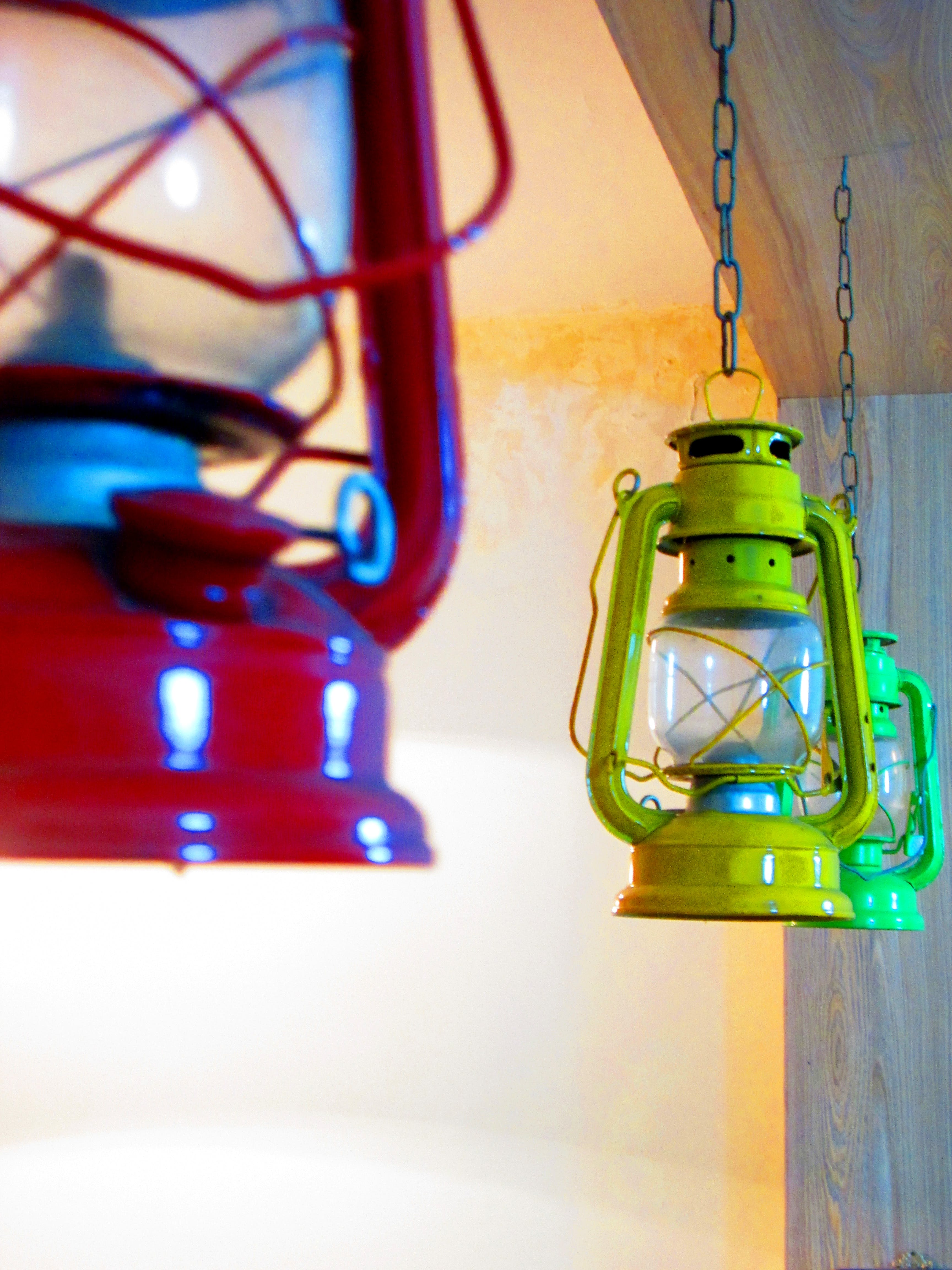 Three Red, Yellow, and Green Gas Lantern Hanging on Ceiling