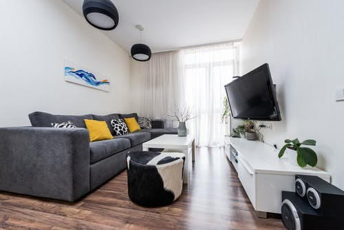 Comfortable gray sofa with yellow pillows placed in light living room in front of TV hanging on wall in modern apartment