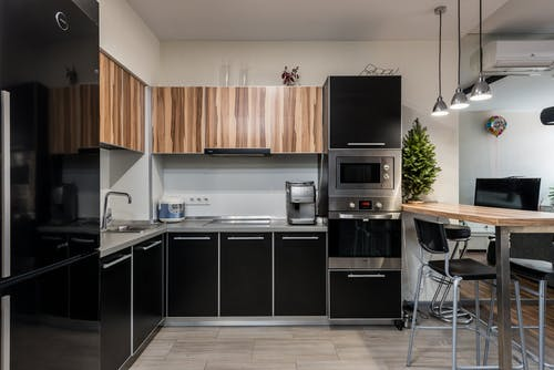 Wooden table with chairs placed near cupboards and counter with sink and appliances in modern kitchen with kitchenware in apartment