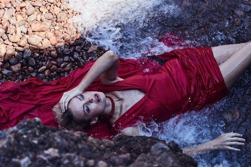 Woman in Red Dress Lying on Rock