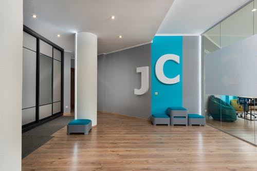 Comfortable poufs placed near wall with J and C letters in modern corridor with column near glass walls in contemporary business center