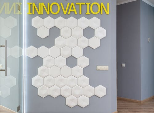 White geometric decorations on wall with yellow Innovation inscription in hallway of modern office building near glass door of room