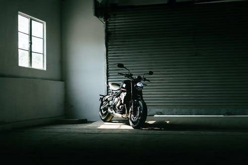Black Motorcycle Parked Beside White Wall