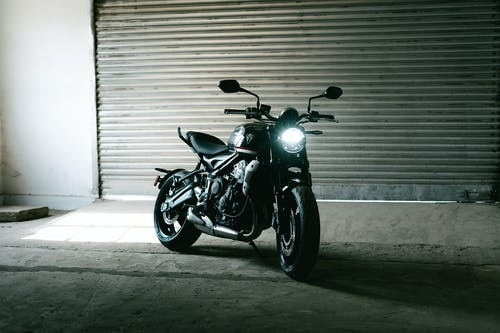 Black and Silver Cruiser Motorcycle Parked Beside Roll Up Door