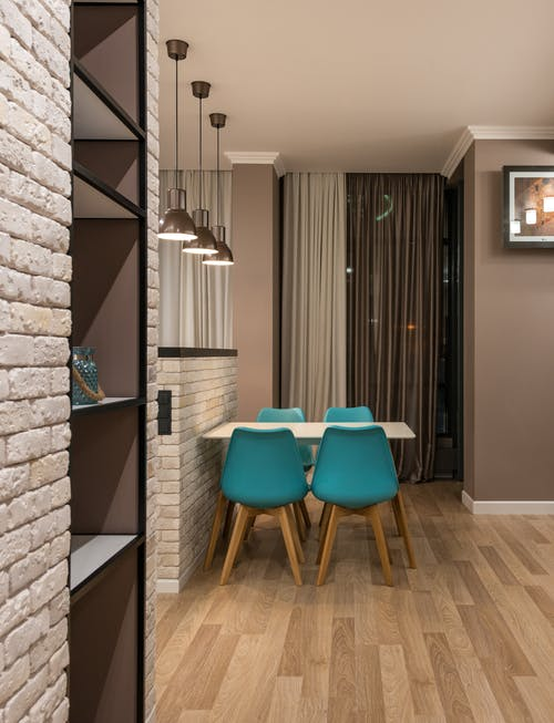Turquoise chairs at table placed near window with curtains in modern spacious apartment with shelves and decorative white brick wall