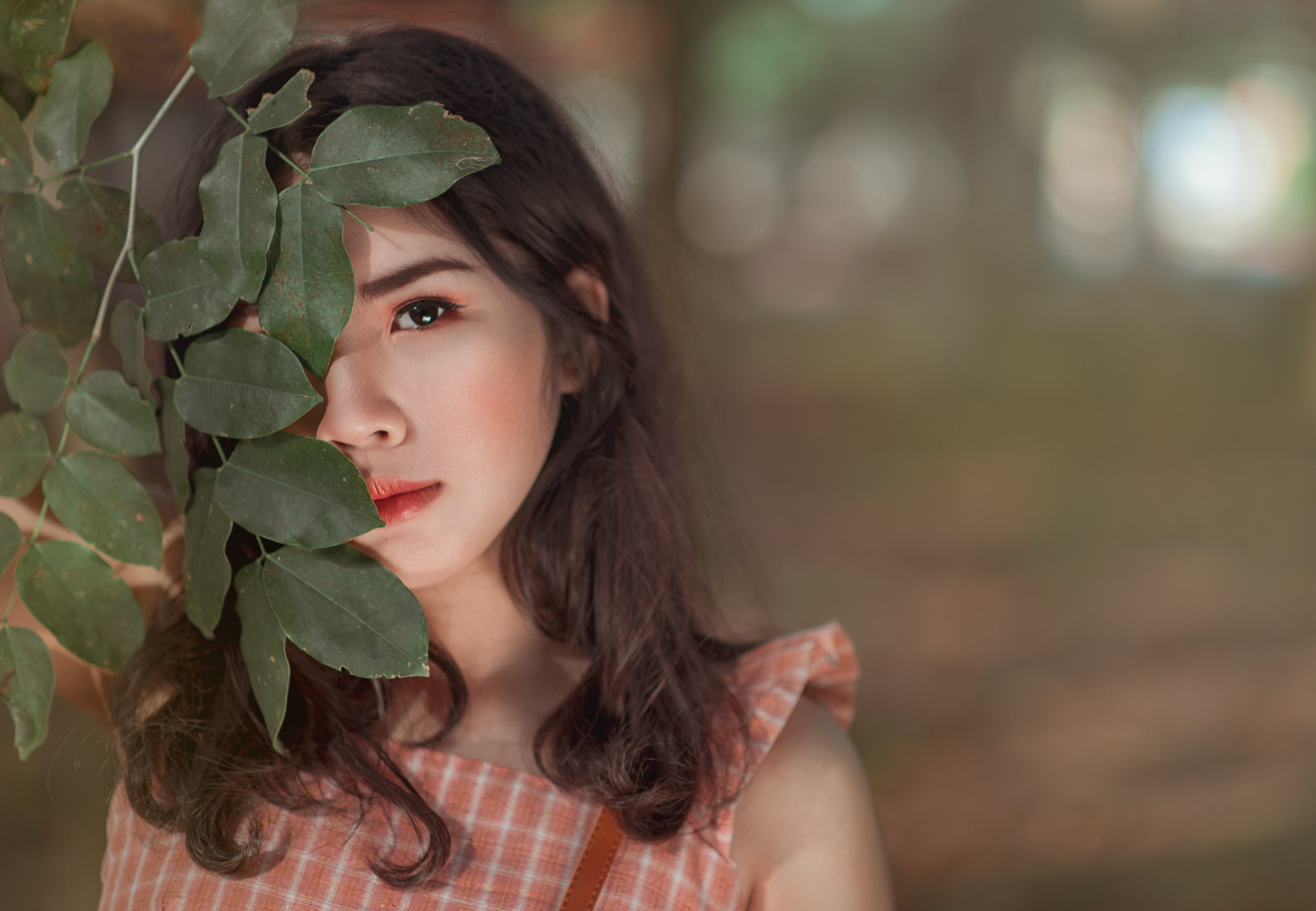 Woman Wearing Pink Sleeveless Top Behind Leaves
