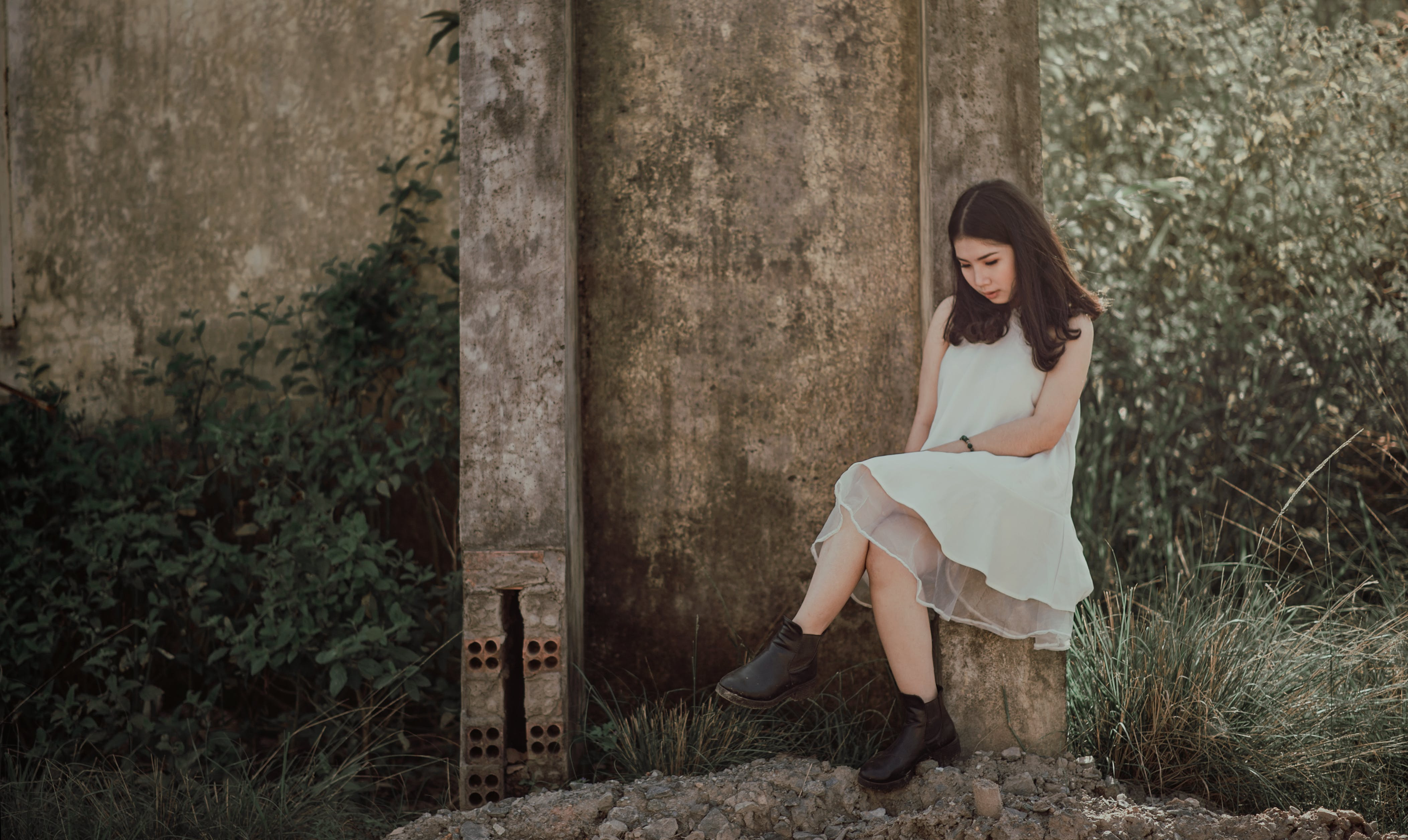 Woman Sitting on Slab Near Brown Wall