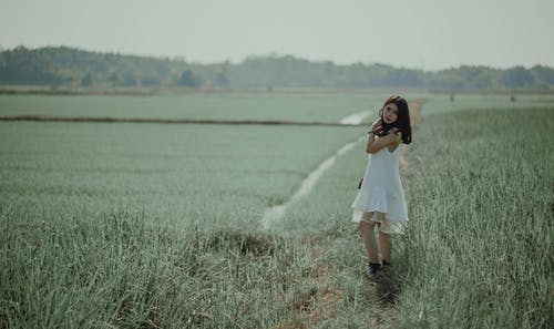 Woman in White Sleeveless Dress on Grass Field