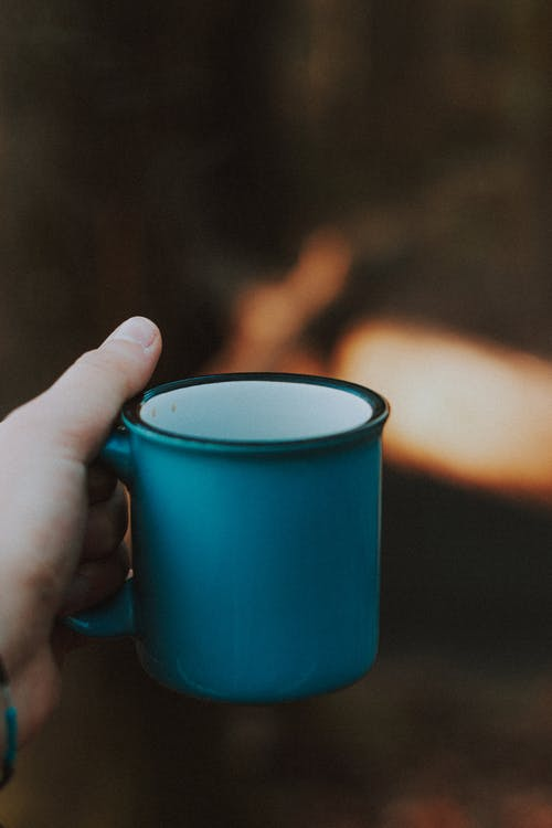 Crop anonymous person showing ceramic blue mug of aromatic hot beverage on blurred background