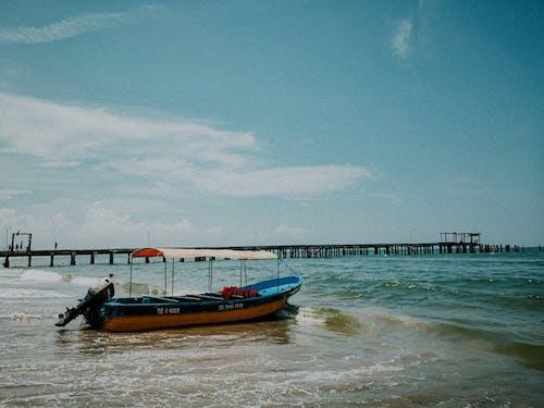 Blue and Orange Boat on Sea Under Blue Sky