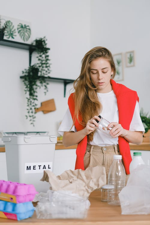 Serious female standing at table with used plastic bags and bottles near egg boxes and paper while taking off lid from glass jar sorting trash