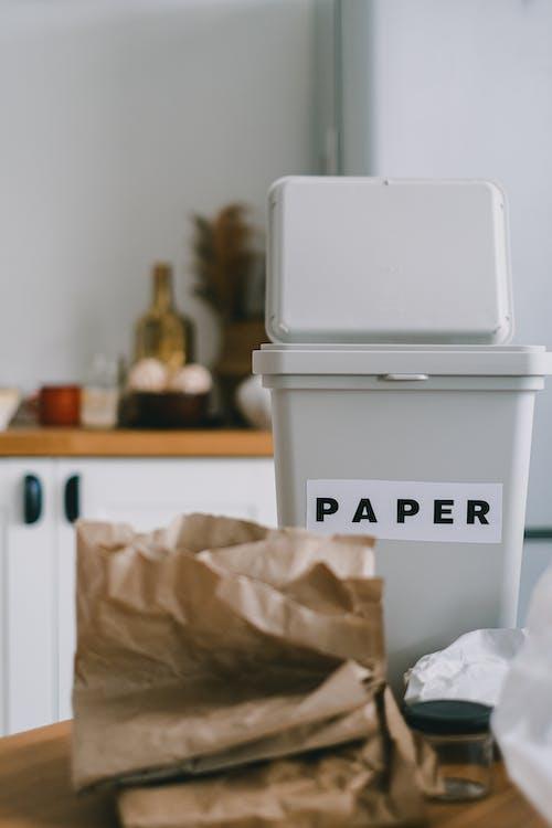 Folded crumpled paper near bin on table