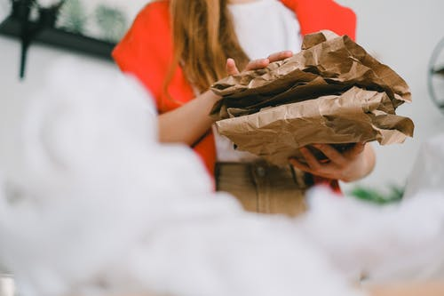 Low angle of crop anonymous female standing with heap of crumple paper while separating trash for recycling