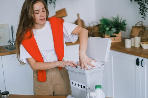 Happy woman sorting trash in bin